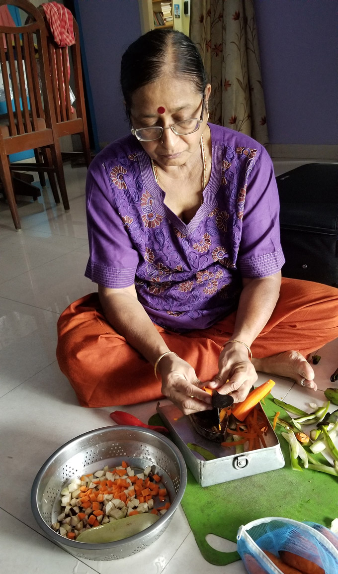 Amma uses a traditional boti knife to cut vegetables while sitting on the floor.