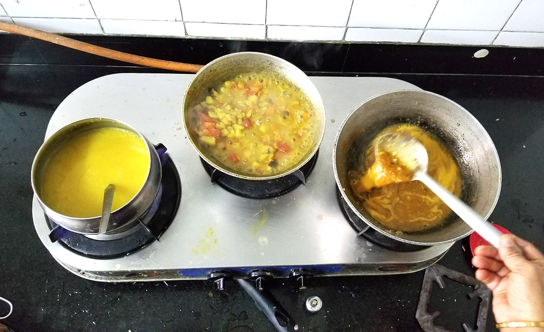 Pots on Amma's stove. Each pot (lentils, diced vegetables, and tamarind), will be combined to make South Indian kootu.
