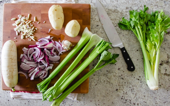 celery, potato, onion, and garlic on chopping board for cream of celery soup